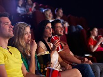Young people sitting in multiplex movie theater, watching movie,