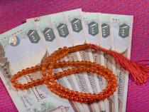 UAE dirham currency notes and a rosary - sharia finance objects