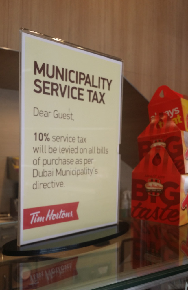A notice about the new tax/fee inside Tim Hortons on Sheikh Zayed Road, Dubai