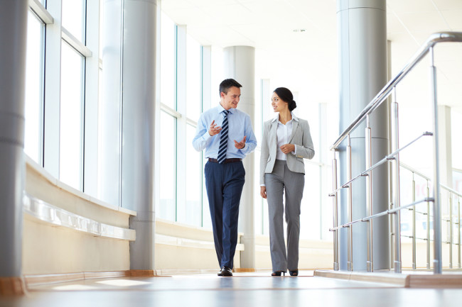 Confident business partners walking down in office building and