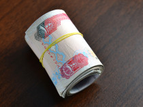 Hundred dirham notes rolled and tied with rubber band.