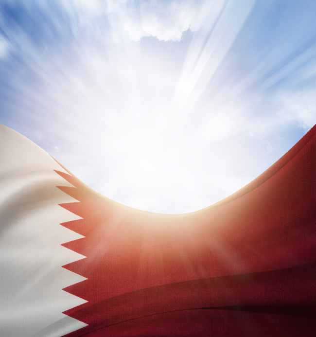 Qatar flag in front of bright sky