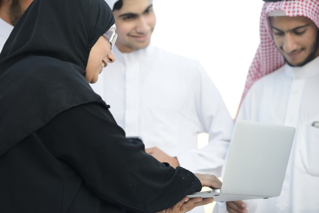 Young Arabic Muslim business woman leading group of Middle easte